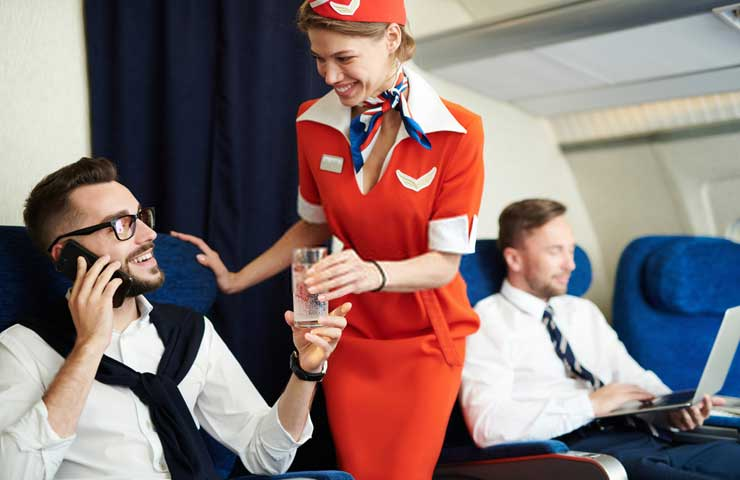 A-flight-attendant-serving-a-glass-of-water-to-a-passenger